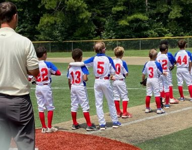 Belonging \ Epidermolysis Bullosa News \ Jonah puts his arm around his brother, Gideon, as they line up with teammates for the National Anthem